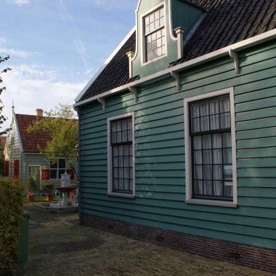 2 green wooden Zaan houses, with a fountain in the courtyard. Located on the Lagedijk